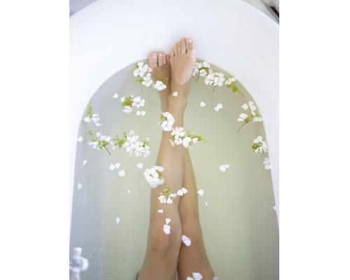 Pieds dans une baignoire avec des fleurs