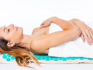 femme couchée sur un tapis d'acupression